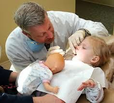 Small child undergoing dental procedure while holding doll for comfort