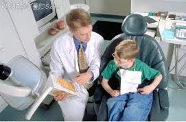 Dentist discussing procedure with child patient